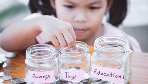 Little girl placing coins in savings jars